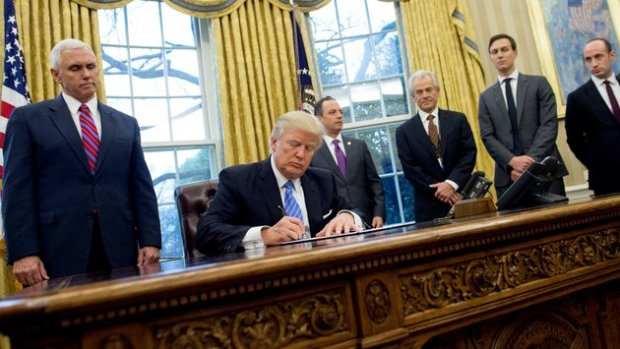 US President Donald Trump signs an executive order in the Oval Office of the White House in Washington, DC, January 23, 2017. Trump on Monday signed three orders on withdrawing the US from the Trans-Pacific Partnership trade deal, freezing the hiring of federal workers and hitting foreign NGOs that help with abortion. / AFP / SAUL LOEB        (Photo credit should read SAUL LOEB/AFP/Getty Images)